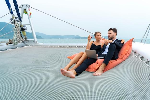 Luxe ontspannen paar reiziger in mooie jurk en suite zitten op bean bag en kijk naar de computer Premium Foto