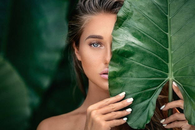Luxe portret van een mooie jonge vrouw met natuurlijke make-up heeft een groot groen blad op wazig groen Premium Foto