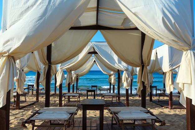 Luxe strandtenten luifels op het witte zandstrand van het ochtendparadijs (pescoluse, salento, puglia, zuid-italië). het mooiste zeezandstrand van apulië. Premium Foto