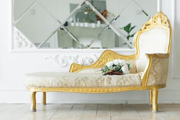 Luxe vintage bank met goud bij de spiegel, mooi klassiek interieur Premium Foto