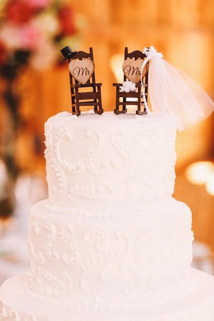 Luxueuze bruidstaart versierd met kleine schommelstoelen Gratis Foto