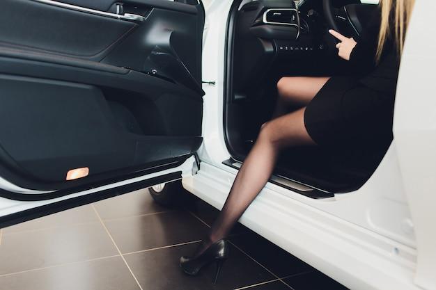 Luxueuze damezitting met de deur open in de witte auto. Premium Foto