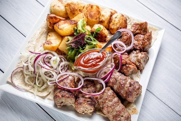 Lyulyakebab met rode saus, ui en aardappels op witte plaat Premium Foto