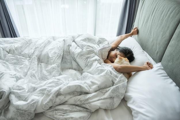Maak de vrouw en kat wakker in bed in de ochtend Premium Foto