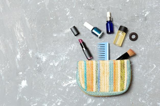 Maak omhoog producten die uit schoonheidsmiddelenzak op grijze cementachtergrond morsen met lege ruimte voor uw ontwerp Premium Foto