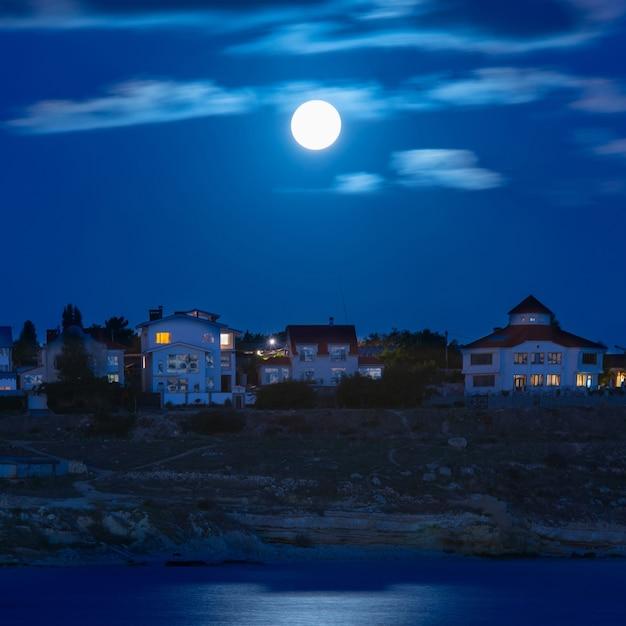 Maan over de rivier bij de stad met blauwe lucht en wolken Premium Foto