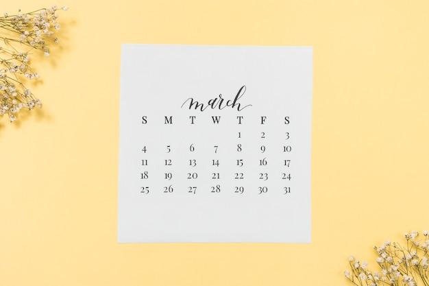 Maart-kalender met bloemtakken op lijst Gratis Foto