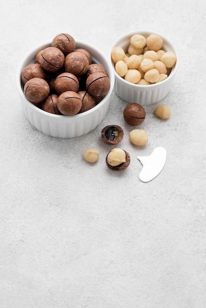Macadamia-noten en chocolade in kommen kopiëren ruimte Premium Foto