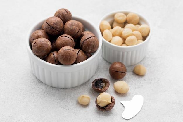 Macadamia-noten en chocolade in witte kommen Premium Foto