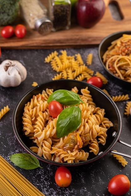 Macaroni gebakken met tomaten en basilicum in de pan Gratis Foto