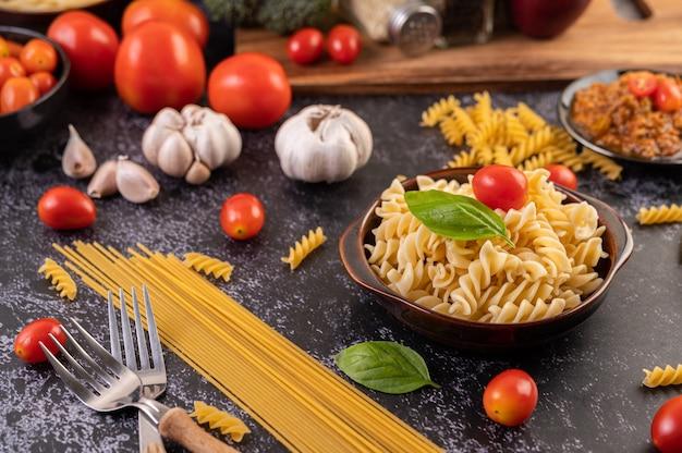 Macaroni gebakken met tomaten en basilicum op een grijze plaat. Gratis Foto