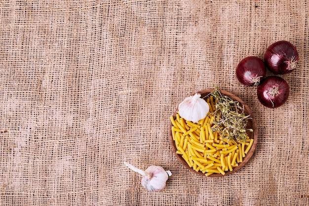 Macaroni, knoflook en uien op bruin oppervlak. Gratis Foto