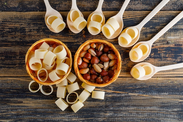 Macaroni pasta in kommen en lepels met pistache en hazelnoot bovenaanzicht op een donkere houten achtergrond Gratis Foto