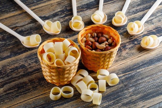 Macaronideegwaren in kommen en lepels met mening van de pistache en van de hazelnoot de hoge hoek op een donkere houten achtergrond Gratis Foto