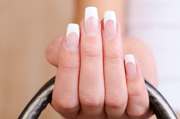 Macro-opname van een mooie elegante vrouwelijke vingers met franse manicure Gratis Foto