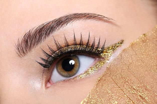 Macro-opname van een vrouw oog met valse wimpers en gele, gouden make-up Gratis Foto