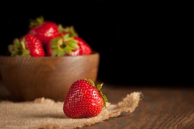 Macrofoto van verse rijpe rode aardbei in een houten kom op rustieke achtergrond. biologische natuurlijke producten. Premium Foto