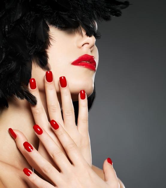 Macrofoto van vrouw met manier rode spijkers en sensuele lippen Gratis Foto