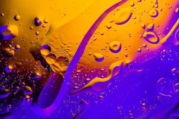 Macroschot van oliebellen met water op kleurrijke achtergrond. Premium Foto