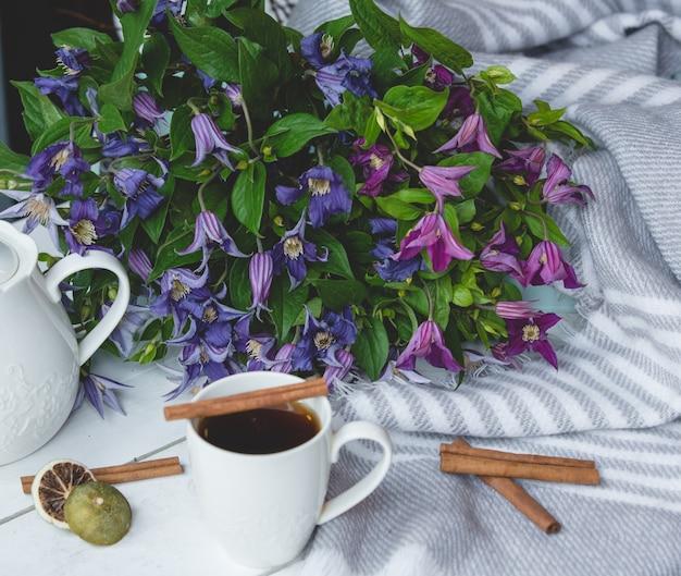 Madeliefjes, een kopje thee en kaneelstokjes Gratis Foto