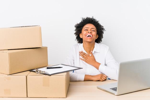 Magazijnbeheerderzitting die leveringen met laptop controleert, lacht hardop terwijl hij de hand op de borst houdt. Premium Foto