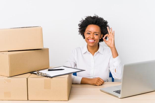 Magazijnbeheerderzitting die leveringen met laptop controleren vrolijk en zeker tonend ok gebaar. Premium Foto