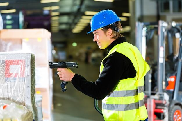 Magazijnier in beschermend vest met behulp van een scanner, staande naast pakketten en dozen in magazijn van expeditiebedrijf een vorkheftruck Premium Foto