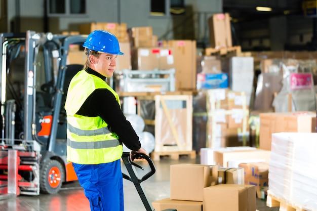Magazijnier in beschermend vest trekt een verhuizer met pakketten en dozen bij magazijn van expeditiebedrijf een vorkheftruck Premium Foto