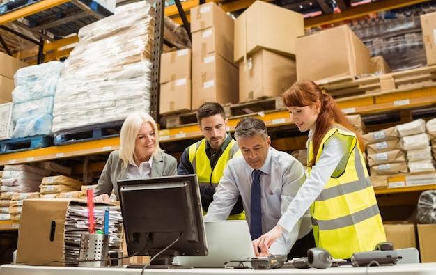 Magazijnmanagers en arbeider die aan laptop werken Premium Foto