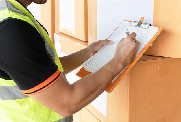 Magazijnmedewerker hand houden klembord inspecteren checklist details van de verzending Premium Foto