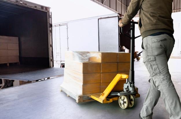 Magazijnmedewerker lossen palletzending goederen in een vrachtwagen. levering en transport van vrachtvracht. Premium Foto
