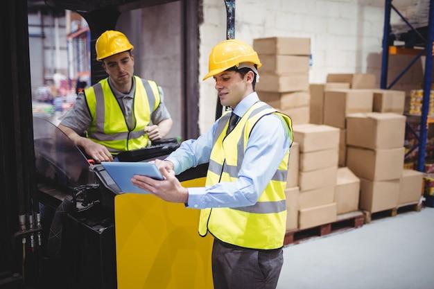 Magazijnmedewerker praten met heftruckchauffeur in magazijn Premium Foto