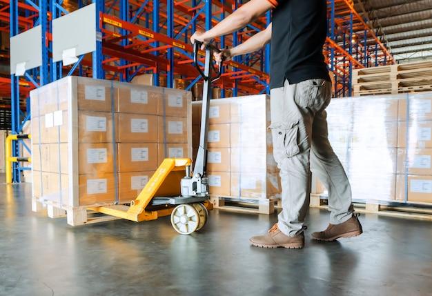 Magazijnmedewerker werkt met handpallettruck en vracht in magazijn. Premium Foto