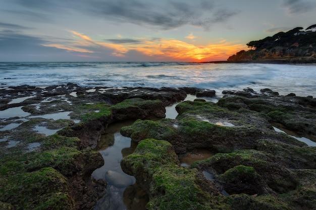 Magische zonsondergang op zee in portugal. stenen mooie vorm op de voorgrond. Premium Foto