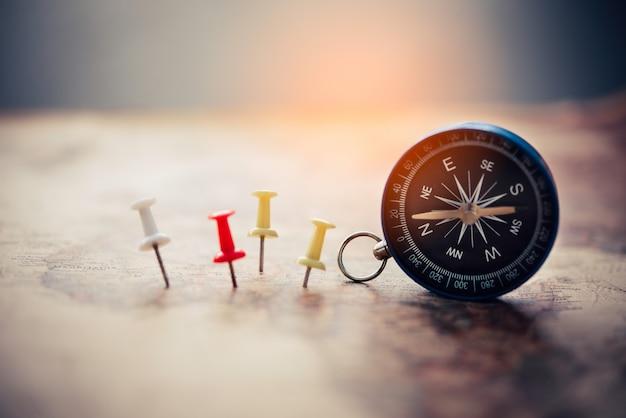 Magnetisch kompas en borduurnaald staat op de kaart. op een wereldkaart conceptueel van wereldwijde reizen Premium Foto