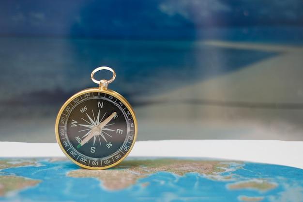 Magnetisch kompas op wereldkaart, concept reis en bestemming, macroreis - beeld Premium Foto