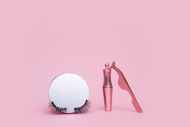 Magnetische nepwimper in spiegelkit, eyeliner, pincet geïsoleerd op roze Premium Foto
