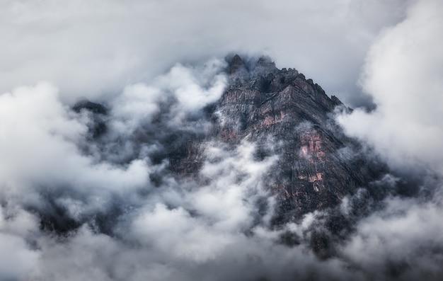 Majestueuze scène met bergen in wolken in donkere avond Premium Foto