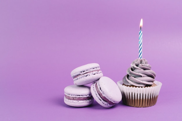 Makarons dichtbij cupcake met kaars Gratis Foto