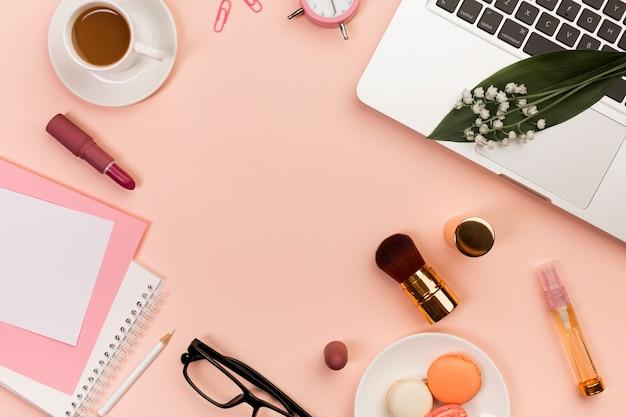 Makarons, make-upproducten, spiraalvormige blocnotes, koffiekop en laptop op perzik gekleurde achtergrond Gratis Foto