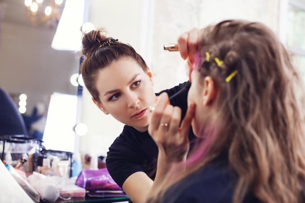 Make-up artiest mascara toe te passen op de wimpers van het model Premium Foto