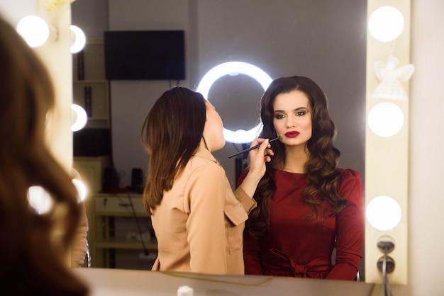 Make-up artiest professioneel doen maakt omhoog van jonge vrouw. school van visagisten Premium Foto