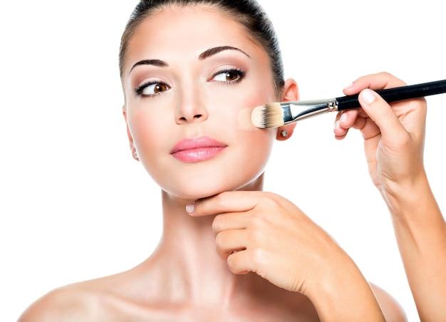 Make-up artiest vloeibare tonale foundation toe te passen op het gezicht van de vrouw Gratis Foto