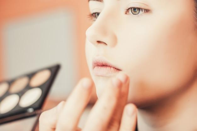 Make-up artist doet make-up van een mooi jong meisje in de studio Premium Foto