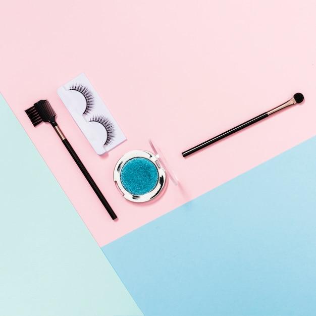 Make-up kwasten; wimpers en blauwe oogschaduw op roze; blauwe en lichtgroene achtergrond Gratis Foto