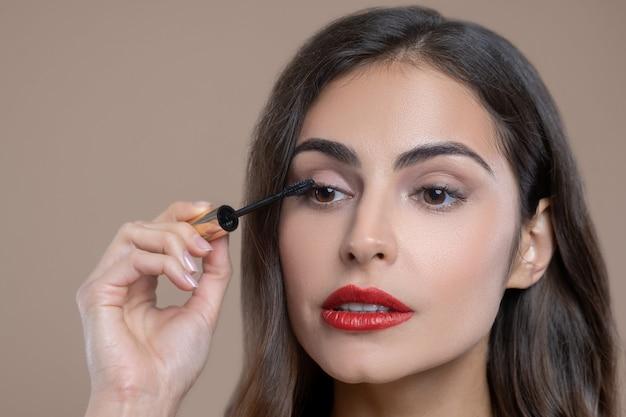 Make-up, ogen. gerichte bruinogige donkerharige vrouw met rode lippen die applicator van de mascaraholding dichtbij haar oog toepast Premium Foto