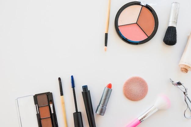 Make-up oogschaduw palet; borstel; spons; lippenstift; mascara op witte achtergrond Gratis Foto