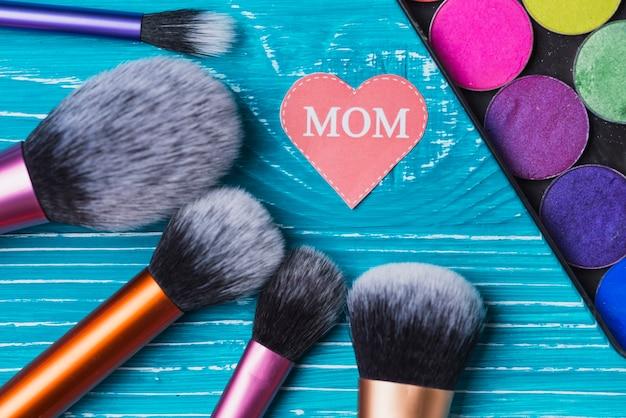 Make-up penselen, gekleurde poeders en document hart voor moederdag Gratis Foto