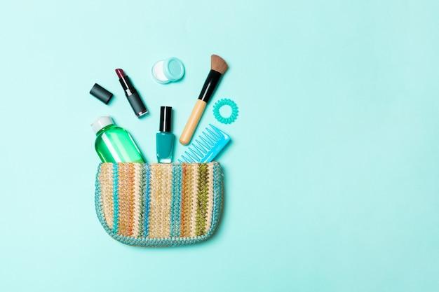 Make-up producten die uit een make-uptas op blauwe pastel komen met lege ruimte voor uw ontwerp Premium Foto