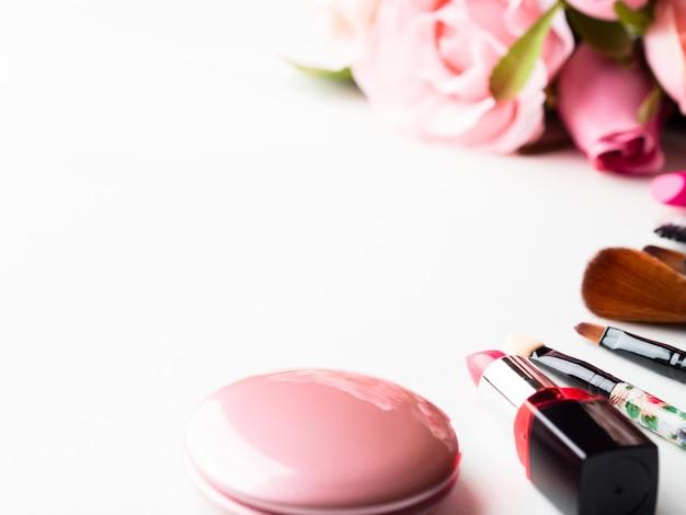 Make-up producten en hulpmiddelen met roze rozen bloemen op wit Premium Foto